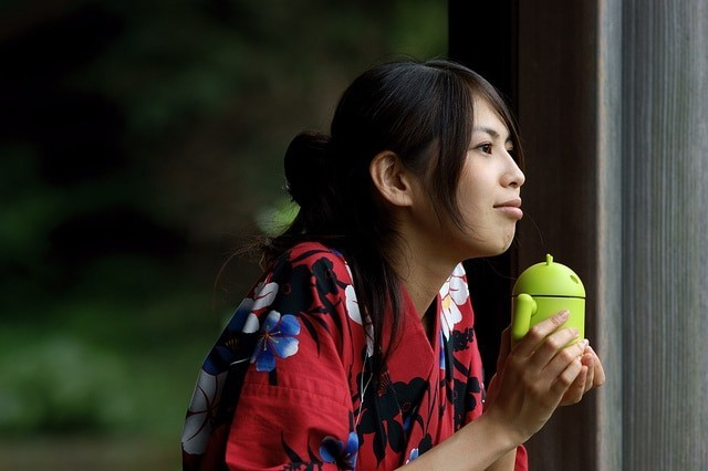 Asiatic girl with Android figurine